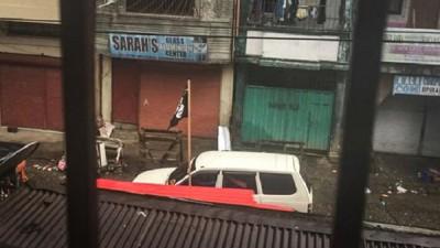 当地一些建筑物和汽车挂有IS的黑色旗帜。