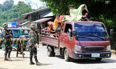 在政府军设置的哨站,军人盘查出城逃难的车辆。