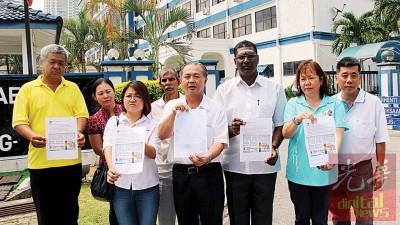 """罗兴强(左五)一行人到警局报警,指""""国际自慰节""""为假消息,与槟州旅游委员会无关。左三为林秀琴,右二起为张君仪及雷尔。"""