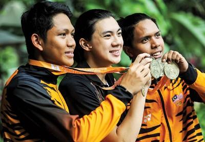 ●赛益迪哈尼夫(右起)和队友刘维政(译音)及瓦菲克手捧25米运动手枪团体金牌庆祝。