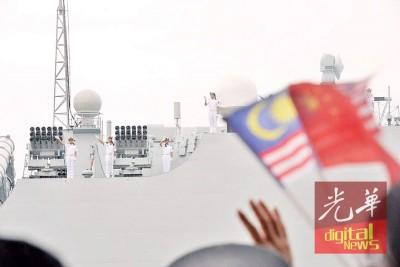英姿飒爽的海军竖立在舰上,向岸上的群众挥手致意。
