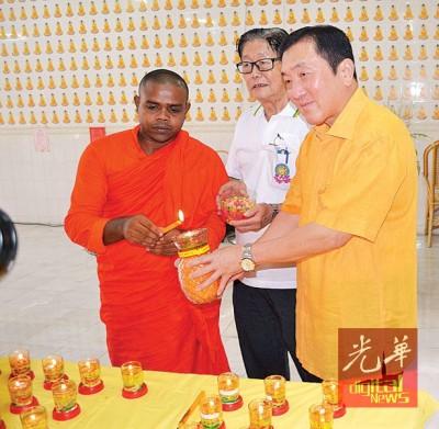 黄家泉(右)出席怡保佛法社卫塞节庆典主持亮灯仪式。