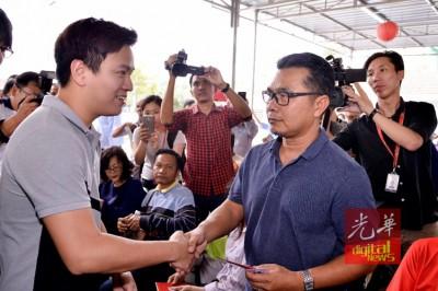 """李宗圣(左)将""""红包""""交投资者手上。"""