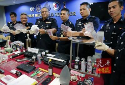 旺鲁曼(左2)与立功警官星期三在记者会出示起获的假钞与疑犯的作案工具。