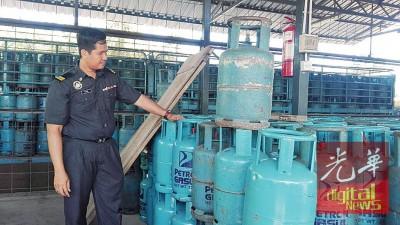执法人员展示起获的煤气桶。