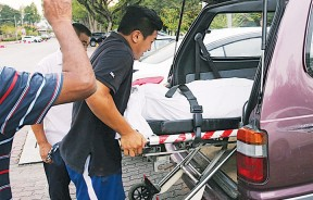 死者的遗体被抬上车准备送往医院太平间。