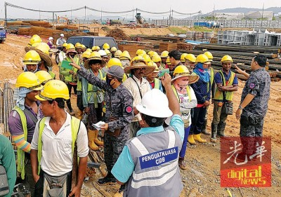 移民局派遣执法官员,随队到建筑工地检查外劳准证。