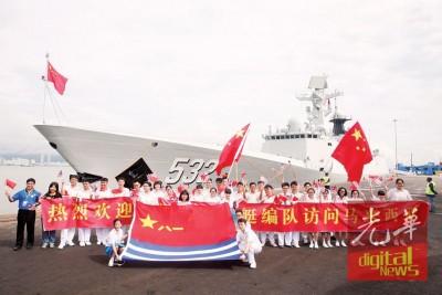 中学生张开欢迎横幅与军舰合影。