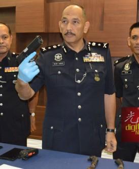 米尔法立(中)出示警方起获的一把假枪支,左为鲁斯兰及纳伊(右)陪同。
