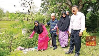 陈国耀(右)陪同村民视察发展商欲赔偿房屋给村民的地段上还未动工。