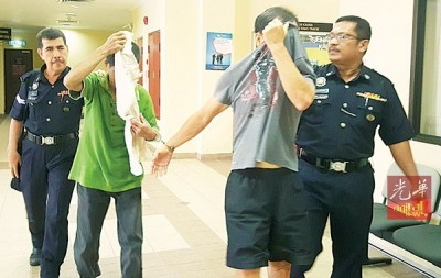 两名被告陈瑞兴与邓清达(人名译音),在面控后被押出法庭。