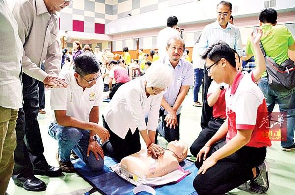 章瑛在红新月会队员指导下,示范心脏复苏术急救法。