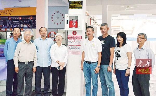 (左起)李添霖、许海明、黄才荣、章瑛、黄英福、黄英源、黄丽英、林楚德一同为明德正校AED装置进行启动仪式。
