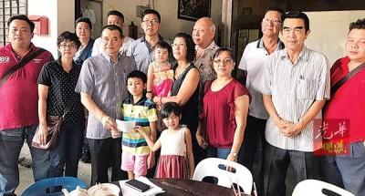 陈德钦(左3)移交赔偿金及抚恤金予已故党员黄松裕之男女。
