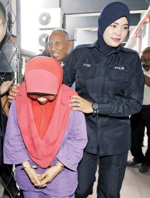 阴被告在于带向法庭面控时,服回避摄影记者的摄影。