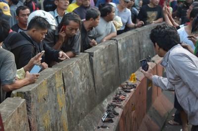 雅加达警方从爆炸现场捡获的人体残肢,吸引大批好奇民众围观。