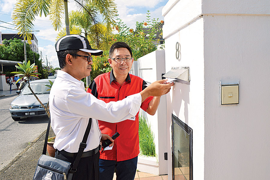 蔡天喜(右)逐户分发大扫除运动的通知传单。左为克里。