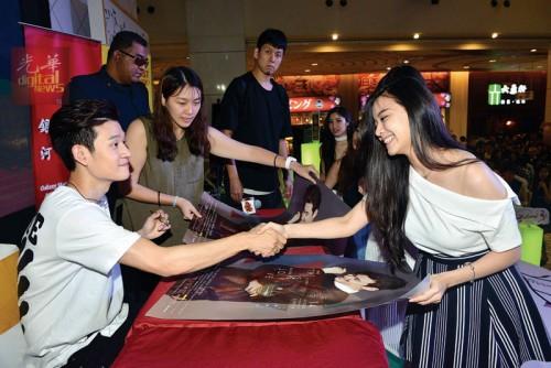 周兴哲为歌迷在加场《This Is Love》个人演唱会的海报上签名。