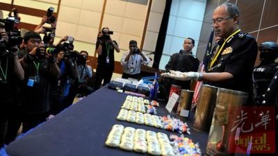 阿祖乃丁(右)向媒体出示以巧克力包装的毒品。