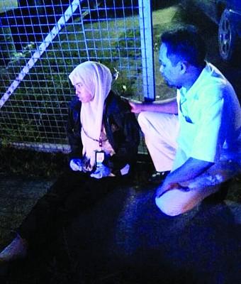 受惊的救护车女医护人员虚弱地坐在马路上,旁人给予安抚。