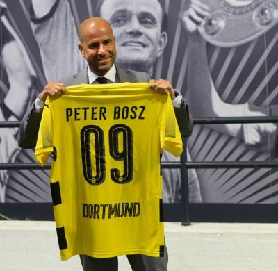 在新闻发布会上,53岁的荷兰教头博斯手持新东家赠送一件印有自己名字的球衣摄影。