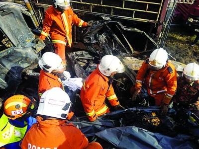 消拯员小心翼翼从休旅车内移出6具焦尸。