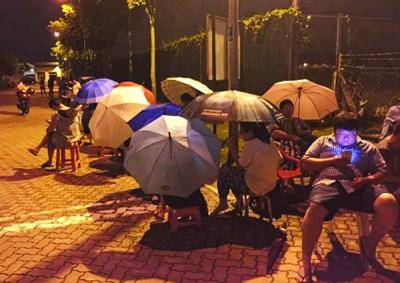 大人为争取学额,不惜到明智华小撑伞彻夜排队。(档案照)