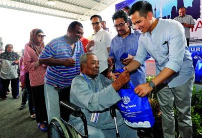 佐哈里(右2)和费沙纳西慕丁(右1从)以及法力克纳西慕丁,通告开斋节用品和援助金予居民。