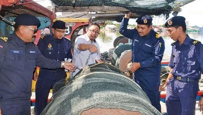 卡欣(中)及执法官员,展示因改装铁链而违例的双拖渔网。