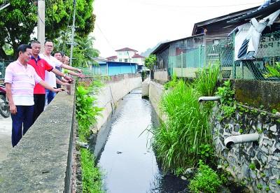 (左起)洪敦吉、胡明彬、胡智胜及居民代表指沟渠提升工程进行一个月就搁置,导致泥土流失沟水流入民宅,倾斜的防洪墙恐会坍塌。