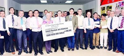 林冠英(左7)在黄汉伟(左5起)及章瑛等人的陪同下,移交模型支票给槟岛内9所国民型中学的董事代表们。