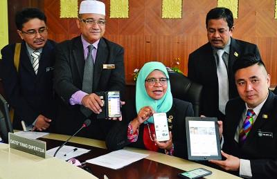 """麦姆娜、罗查理及市议员们展示Better Penang手机应用程序,在""""精明监督系統""""下,当局可第一时间掌握并解决民众投诉。"""