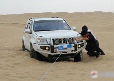 警员与邱男一同把深陷沙漠的车推上路面。