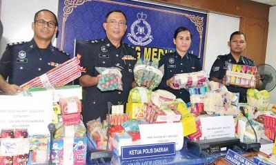 奥玛巴迪亚(左2)与调案官们展示警方所充公的烟花爆竹。
