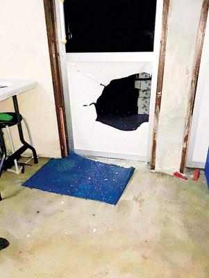 毛贼将已上锁的办事处大门撬开,准备取走财物。
