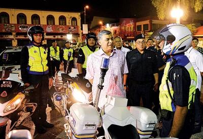 卡立(中)向完成巡逻工作的大型摩托车巡逻队(URB)警员了解最近工作状况。