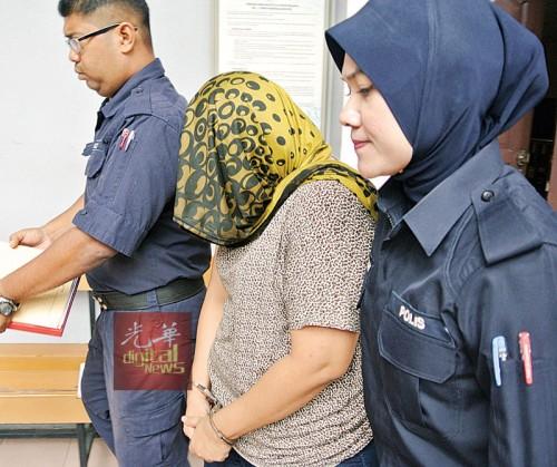 以头巾遮脸的被告莎花玲娜面控后遭庭警押离法庭。