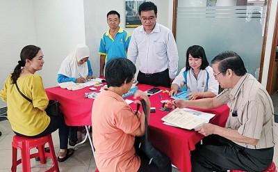黄汉伟(左2)前往马来亚银行亚依淡甘榜峇鲁分行,巡视黄金妈妈计划发放回馈金的情况。