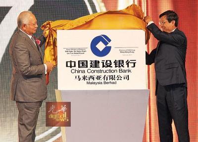 纳吉(左起)与王洪章为中国建设银行(马来西亚)有限公司进行开业揭牌仪式。
