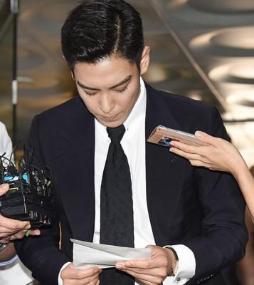 T.O.P现身,看着拟好的稿子向媒体说明。