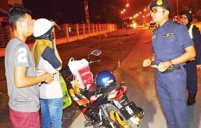 玛哈兹尔(右)向自称借用友人摩托车的25岁巫青问话,该辆摩托车被充公作进一步调查。