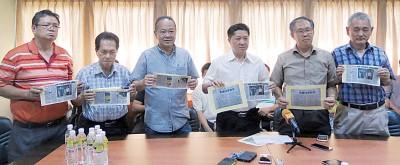 左起蔡成财、施水生、黄荣辉、陈燕翔、陈瑞法,以及曾文益在记者会上展示贸消部已证实米厂没有生产假米的新闻剪报。