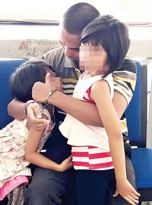 被告莫哈末阿比拉离开法庭前拥抱孩子。