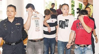 4名被告左起张秋明、黄春斌、郭贤达以及王国良(人名译音)被控不认罪后,被庭警押出法庭等待保外候审。