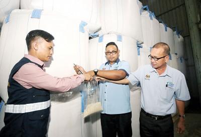 阿都拉欣(右起)和英然在分销及包装厂内抽取白米样本。