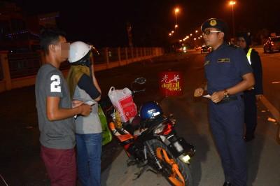 玛哈兹尔(右)向借用友人摩托车的25岁巫青问话,该辆摩托车被充公作进一步调查。