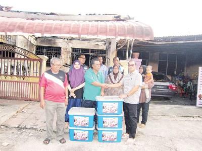 达祖(右)移交援助品给5户受影响的灾民。