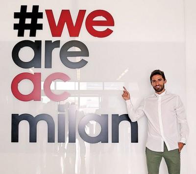 """博里尼完成签约后站在写上""""我们是AC米兰""""巨星宣传海报前开心留影。"""