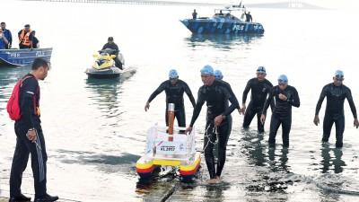 由水警组成的游泳传递队在槟城大桥为背景下,将东运火炬运上岸。