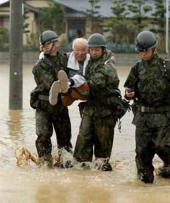 自卫队员把不良于行的老人,逐个从灾区救出来。(法新社照片)
